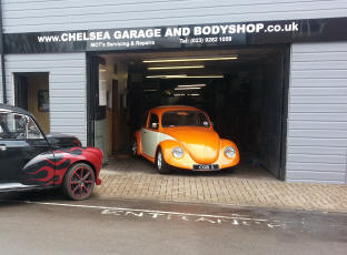 Front of Shop with sign and Resprayed orange volkswagon beetle parked in the garage.
