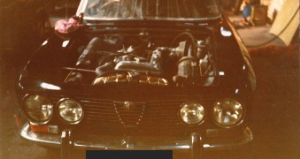 Various pctures of a restored black Alfa Romeo 2000 GTV.